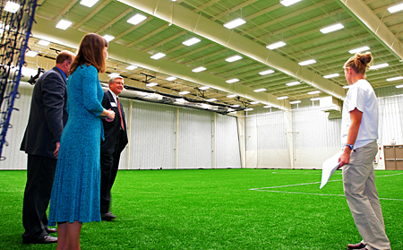 Photo: A student tour guide shows off the broad expanse of artificial grass in the facility's new turf gym.