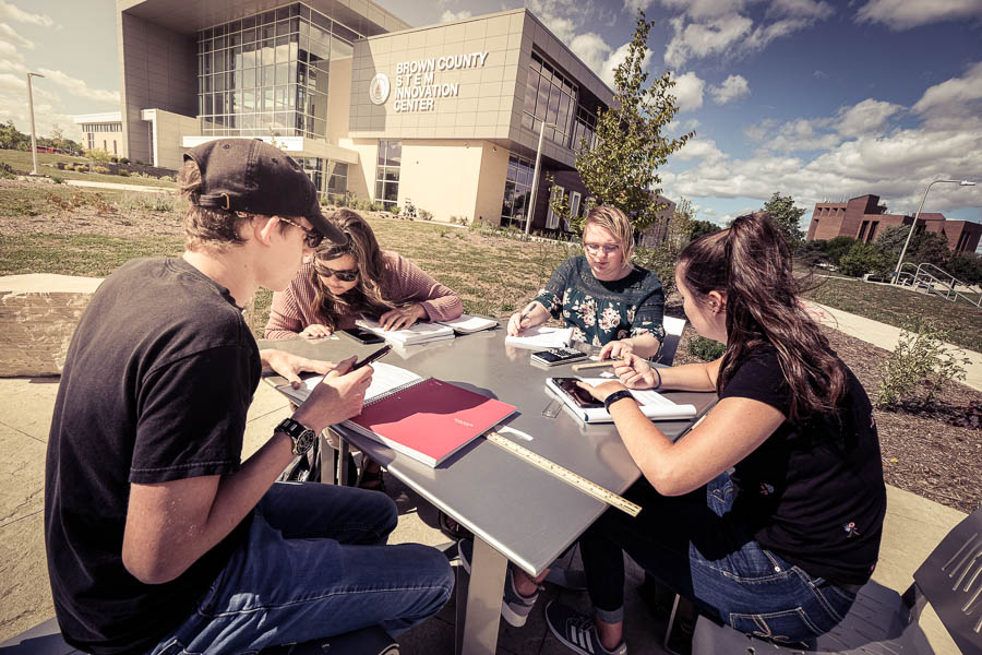 students working outdoors at a table at uwgb