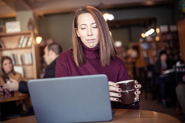 An adult learner works on a laptop in a cafe.