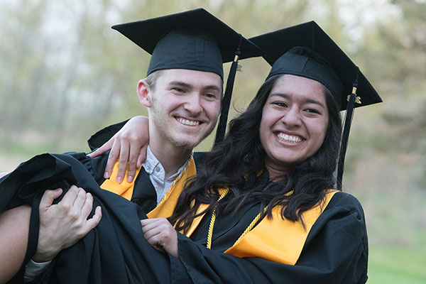 One UW-Green Bay, Manitowoc Campus graduate picks up another graduate in celebration.