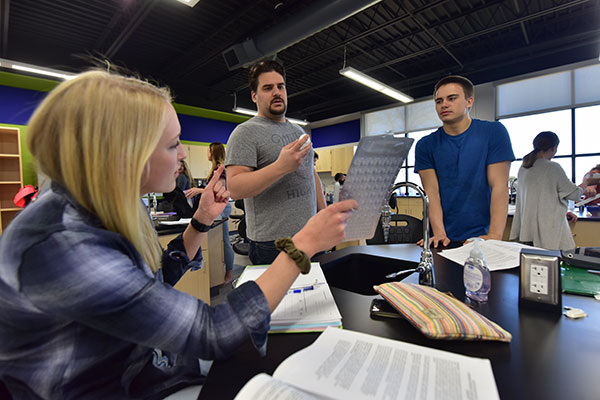 Students and a professor work together in a classroom at the UW-Green Bay, Manitowoc Campus.