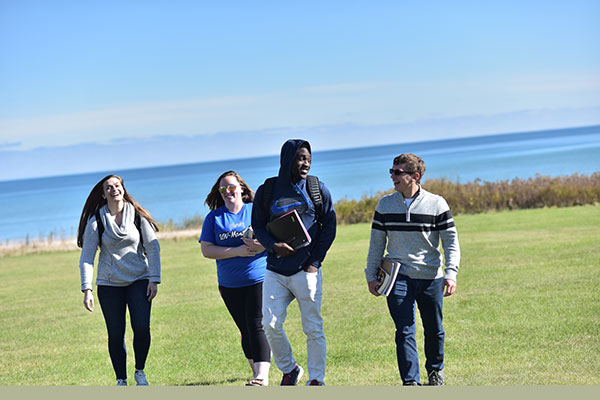 Four UW-Green Bay, Manitowoc Campus students walk across a green space.
