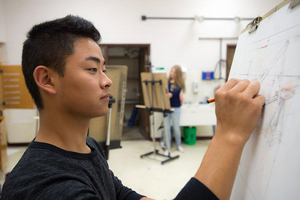 A Marinette Campus student sketches in an art studio.