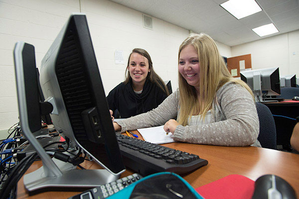 Two Marinette Campus students work together in a computer lab.