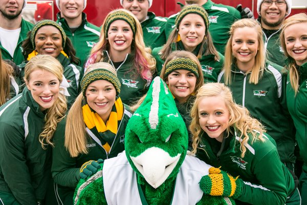 UW-Green Bay cheerleaders pose for a photo with a mascot.