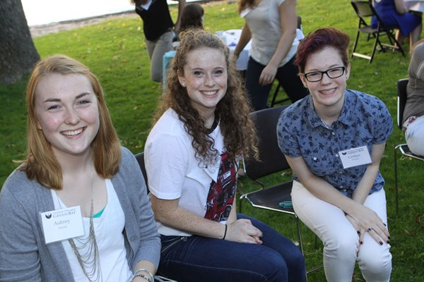 Three UW-Green Bay students smile while sitting outdoors.