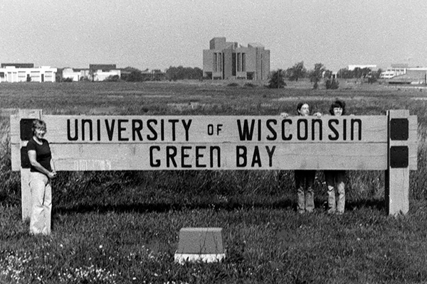 Black and white photo of people with a UW-Green Bay sign