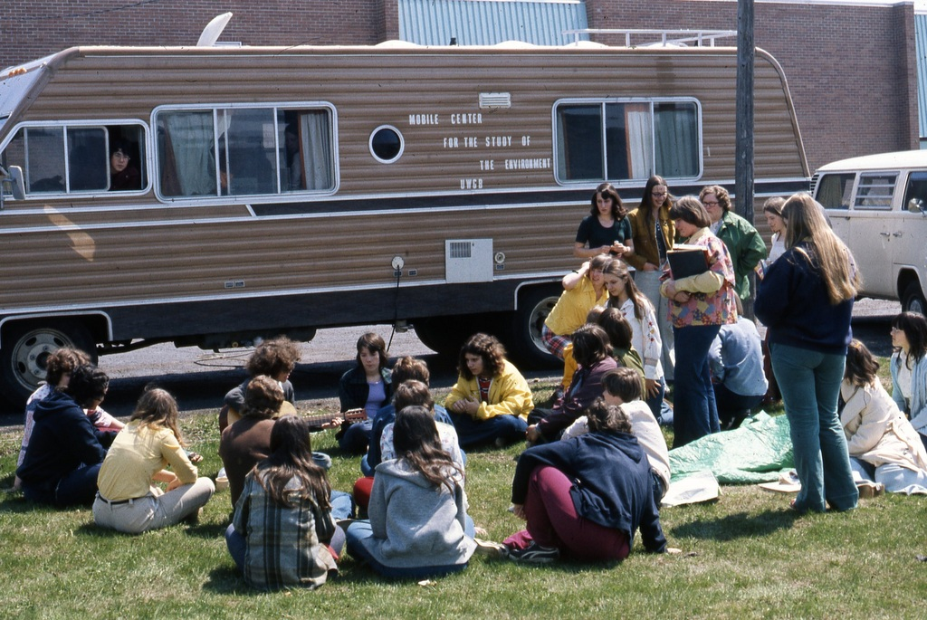 People sitting next to a RV labeled Mobile Center for the Study of the Environment UWGB