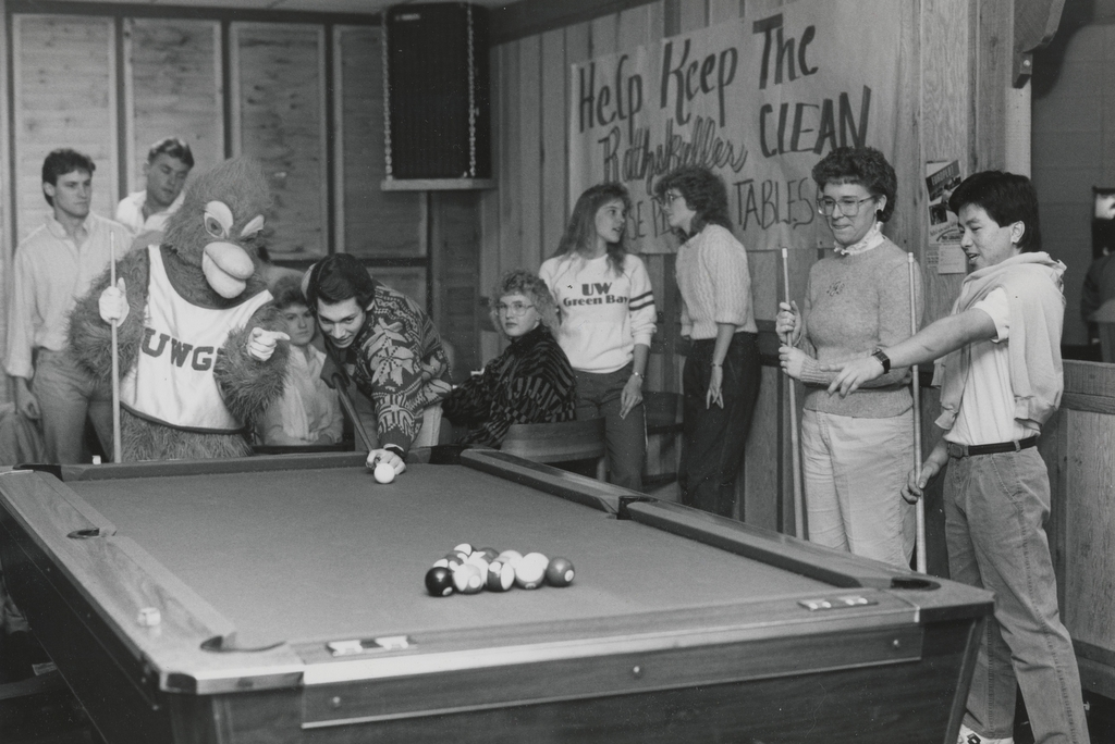 Black and white photograph of people playing pool with the Phoenix mascot