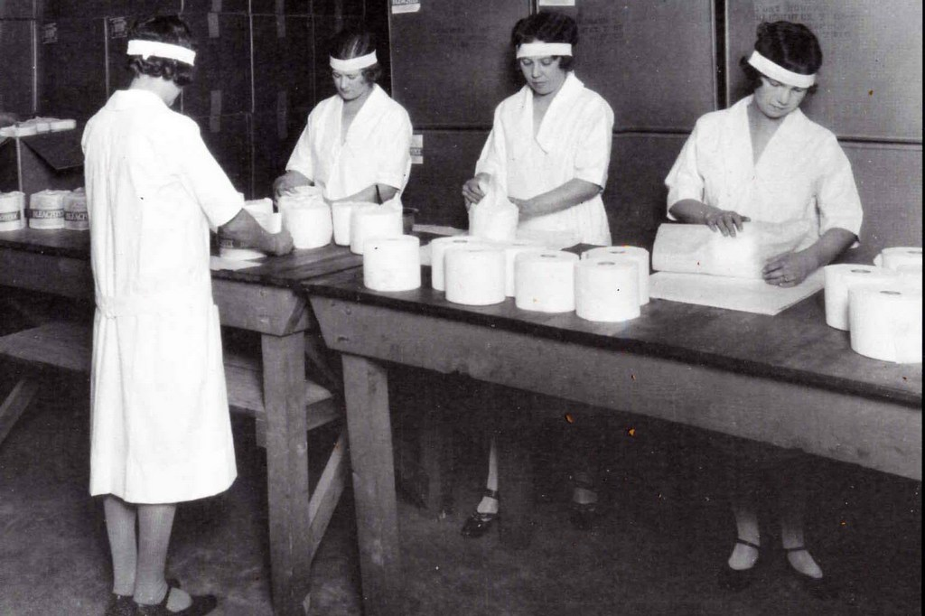 Black and white photograph of women in a factory wrapping toilet paper