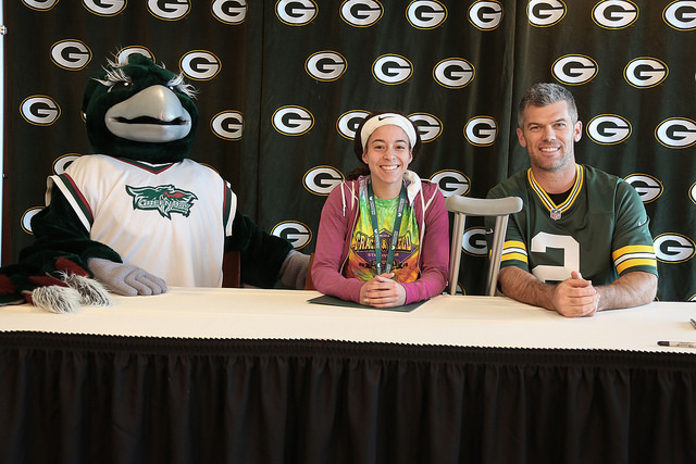 Student signing her letter of intent with Phlash Phoenix and Mason Crosby