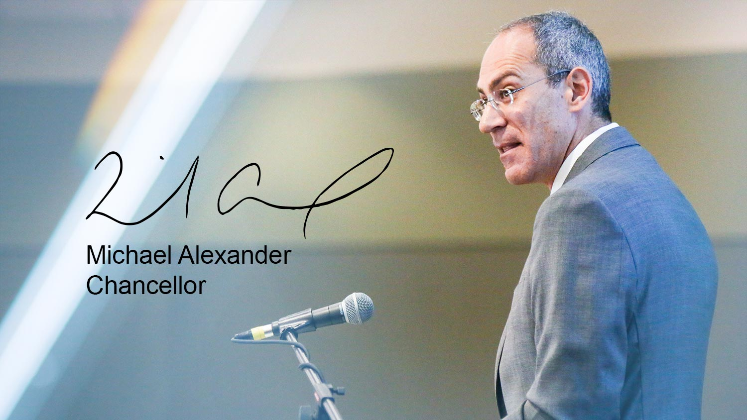 Michael Alexander at a microphone | Signature of Michael Alexander | Michael Alexander, Chancellor