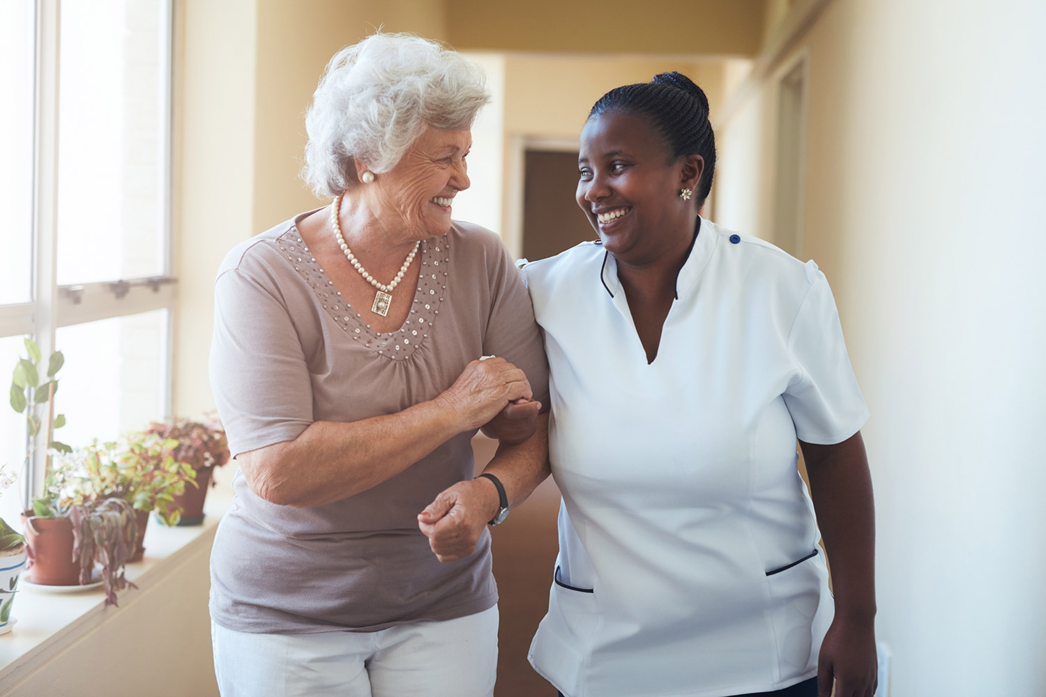 Photo of caregiver and patient walking down a hallway