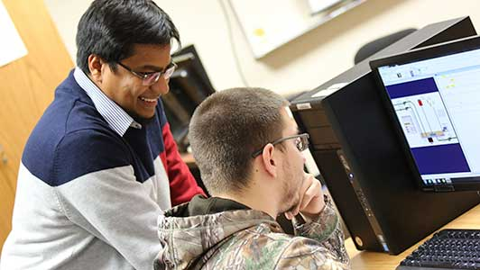 UW-Green Bay's Md Maruf Hossain assisting an engineering tech student at a computer.