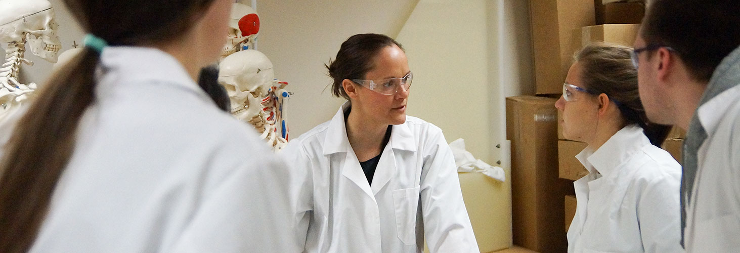 Amanda Nelson with Anatomy students, wearing safety goggles and white lab coats