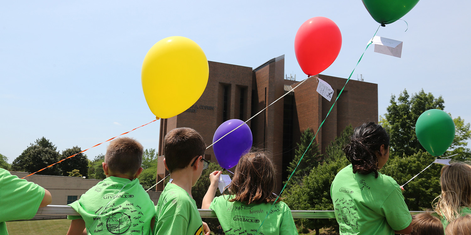 Photo of kids with balloons on campus