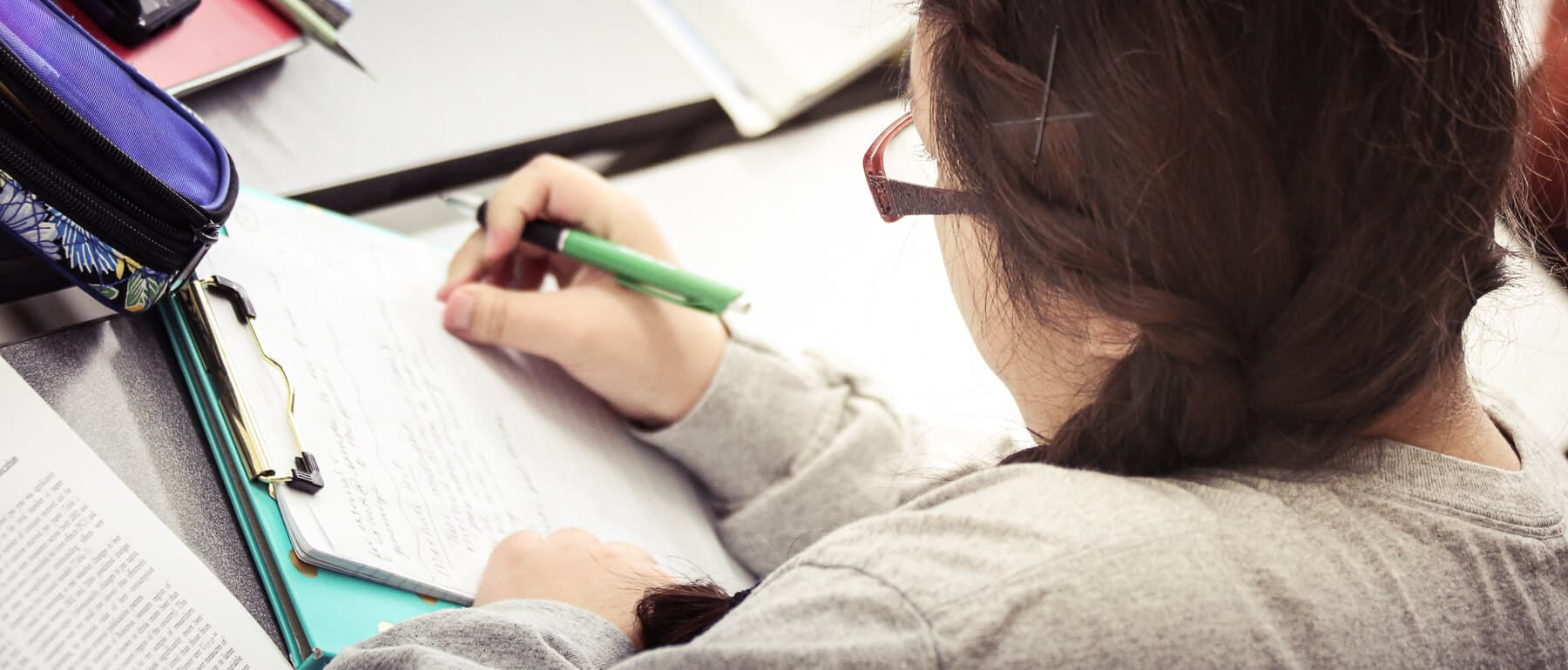 A UWGB student takes notes in class.