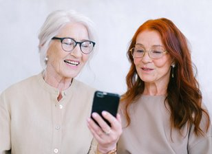 Two older women engaging with cellphone